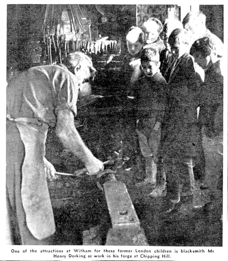 London children visit the forge in Chipping Hill to see the blacksmith, Henry Dorking, at work.