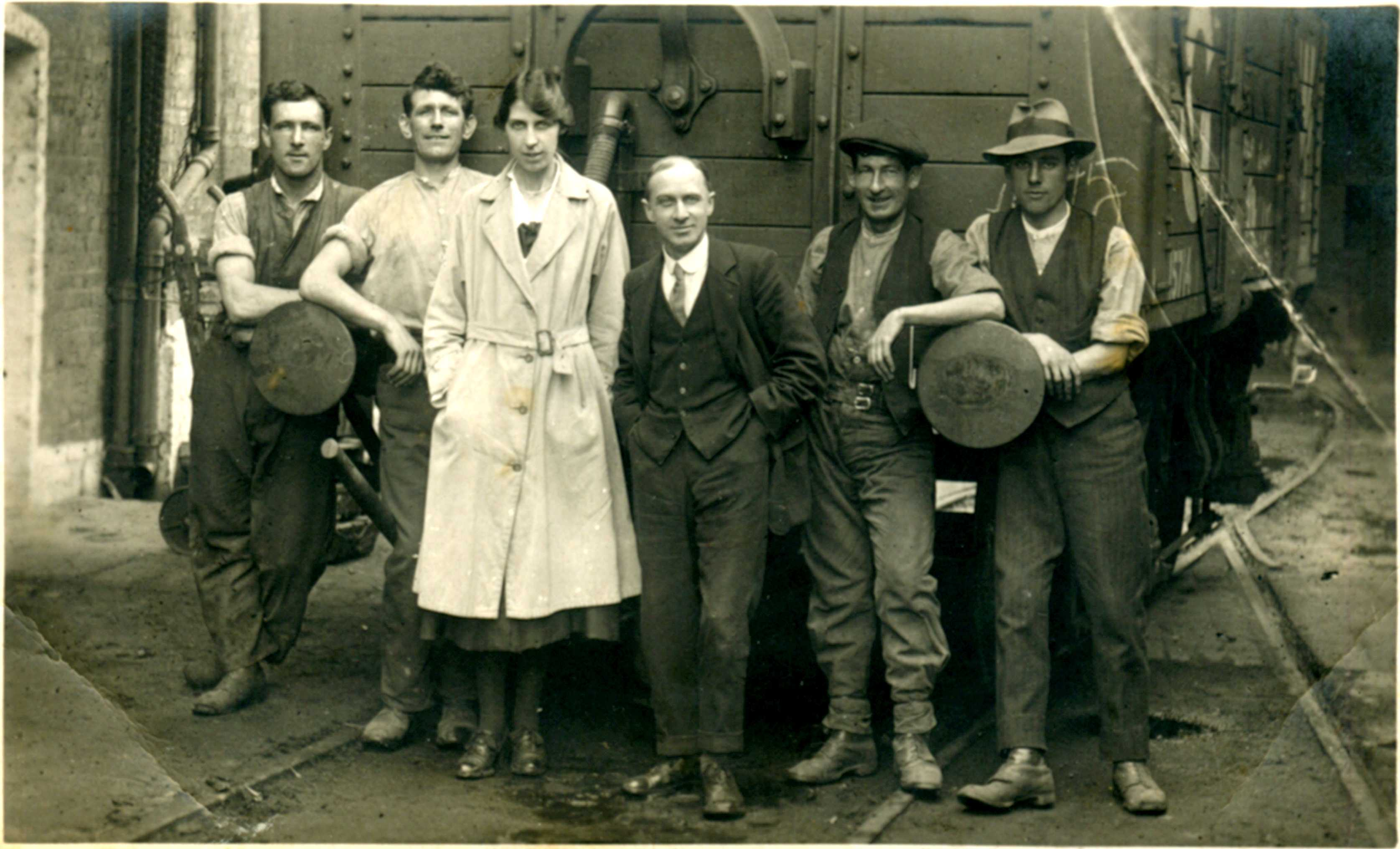 "The inscription is ""Clearing shell cases from Maltings 1920-23"" . A few of the names are given - Bert Colman (far left), Florence Ada Smith (white overall, the subject of this interview), John Youngs (far right). The maltings are the Station Maltings. Railway lines are at the front, and a railway truck behind."