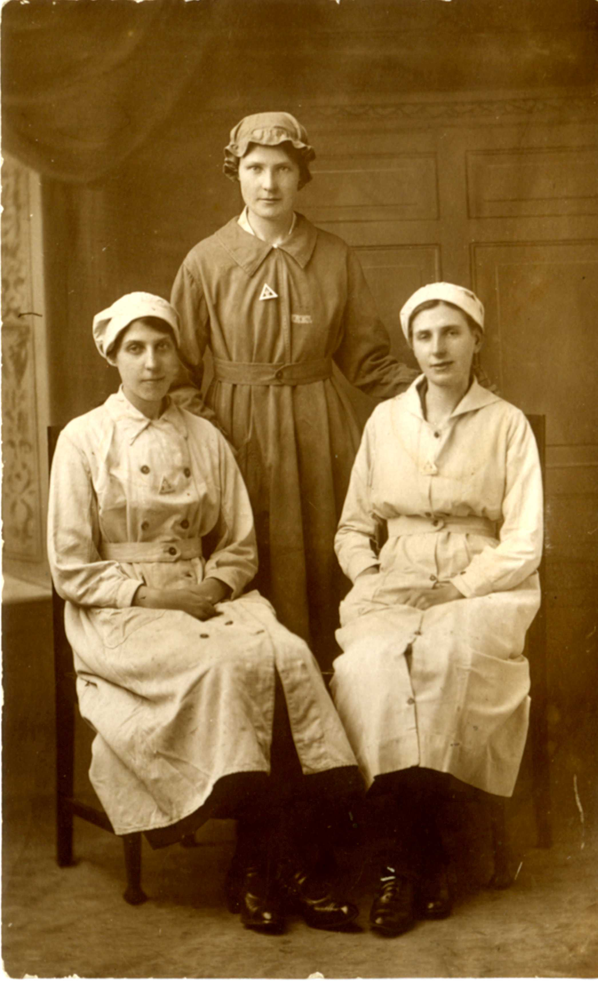 Three Smith sisters. Taken during the First World War. The inscription describes them as 'Charles' 3 sisters' and names them as Ada on the left, Ellie in the centre, and 'Ted Stoneham's wife' on the right. Ada was Florence Ada Smith of Chalks Road, who is interviewed here. It is a studio portrait. They have triangular badges which will be 'On War Service' badges, with a crown in the middle. They were issued in 1916 in brooch form, specially for women. Other badges for this purpose had button-hole fastenings. They are also wearing a uniform, Ellie's being different from the other two. Ada worked at the Station Maltings in munitions; Ted's wife's uniform is the same as hers.